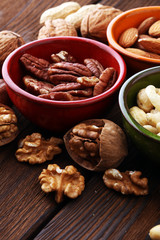 bowls with mixed nuts on wooden background. Healthy food and snack. Walnut, pecan, almonds, hazelnuts and cashews.