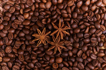 Three stars of anise lie on a large number of coffee beans. A set for cooking a fragrant Arabic drink. The most fragrant spices and coffee. Cooking chocolate Christmas baking with spices.