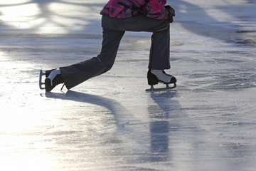 the girl rises after a fall skating on the ice rink.