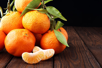 Tangerines with leaves on wooden background. Mandarins Rustic style.