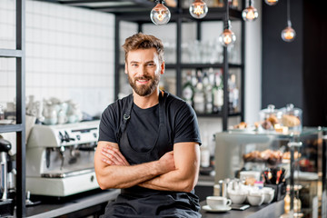 Fototapeta Portrait of a handsome barista in black t-shirt and apron sitting at the bar of the modern cafe obraz