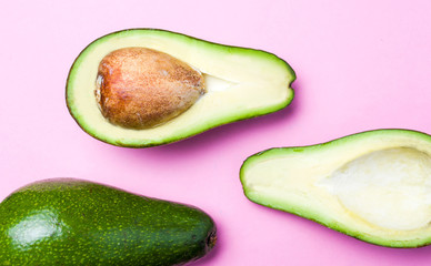 Avocado slices on pink background
