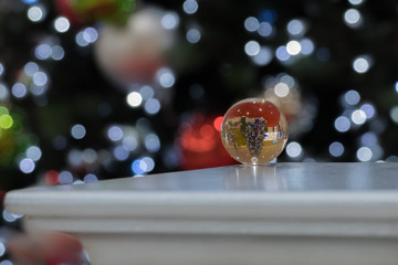 A crystal ball is reflecting a christmas tree