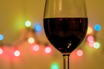 Glass of wine with decorative light in the background