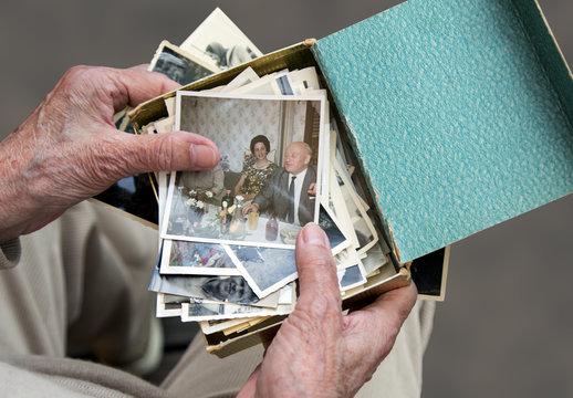 Seniorin betrachtet Fotos aus der guten alten Zeit