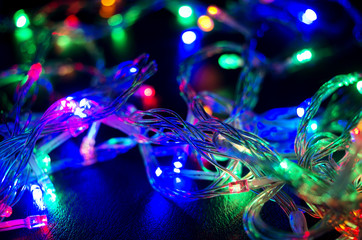 A colorful background with glowing Christmas garland. Selective focus.