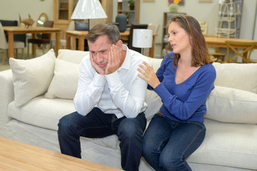 husband disapponted by price of sofa at furniture shop