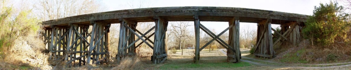 Wood Bridge at Sunset, Sunlight streams under the trestle, wide panorama.