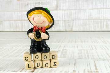 Little chimney sweeper with a horseshoe in his hands, standing on wooden cubes with the words good luck, wooden background and copy space