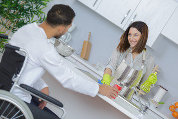 Man in wheelchair talking to woman cleaning kitchen