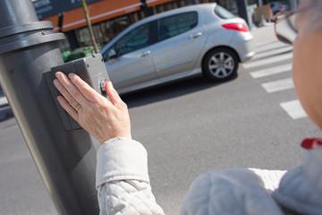 senior lady hand pressing crossroads button