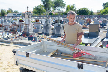 Photo sur Aluminium Cimetiere Cemetery maintenance man loading tools into trailer
