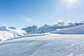 Off-piste ski slope with trace from skis and snowboards at sun winter day. Kavkaz mountains.