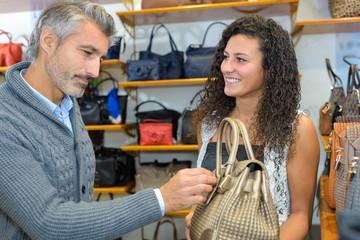 Man and lady in handbag shop