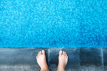 Selfie the feet at the pool side or edge with blue mosaic tiles at the bottom of swimming pool.