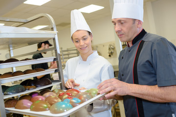chef and assistant prepare delicious pastries in the kitchen
