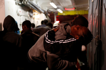 Migrants embrace on the deck of MV Aquarius, a search and rescue ship run in partnership between SOS Mediterranee and Medecins Sans Frontieres, after being rescued in the central Mediterranean 69 nautical miles off the coast of Libya