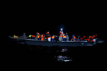 Migrants on a rubber dinghy are rescued by the crew of MV Aquarius, a search and rescue ship run in partnership between SOS Mediterranee and Medecins Sans Frontieres, in the central Mediterranean 69 nautical miles off the coast of Libya
