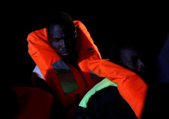 Migrants on a rubber dinghy await rescue by the crew of MV Aquarius, a search and rescue ship run in partnership between SOS Mediterranee and Medecins Sans Frontieres, in the central Mediterranean 69 nautical miles off the coast of Libya