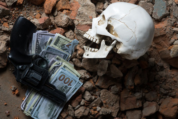 money and a revolver near the skull. Criminal concept