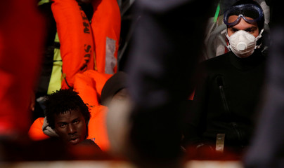 A rescue boat from the Italian Navy frigate Rizzo brings migrants rescued from a rubber dinghy to the MV Aquarius, a search and rescue ship run in partnership between SOS Mediterranee and Medecins Sans Frontieres, in the central Mediterranean 69 nautical m