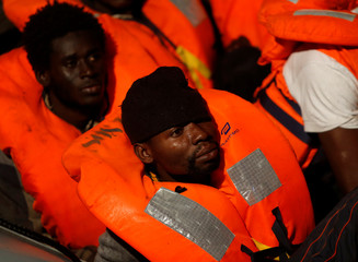 Migrants rescued from a rubber dinghy wait to board the MV Aquarius, a search and rescue ship run in partnership between SOS Mediterranee and Medecins Sans Frontieres, in the central Mediterranean 69 nautical miles off the coast of Libya