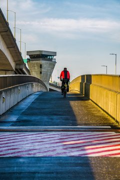 A bicyling riding over a Bridge in the city at sunrise