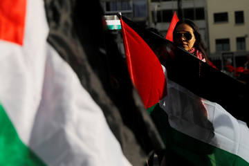 A woman holds a Palestinian flag next to supporters of Palestine while demonstrating against U.S. President Donald Trump's recognition of Jerusalem as Israel's capital, outside the U.S embassy in Mexico City