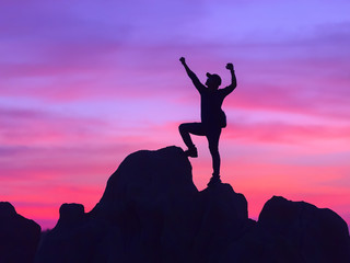 Silhouette of Man Celebration Success Happiness on a Stone at sunset time.
