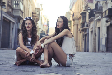 Beautiful girls sitting in a street