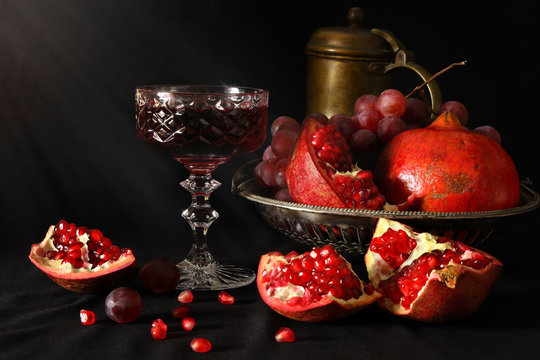 Still life with pomegranates, grapes and a glass of wine