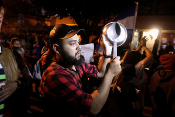 An opposition supporter holds a pot during a demonstration over a disputed presidential election in Tegucigalpa