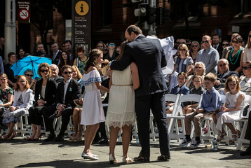 Chloe and Paul Smith, daughter and husband of Katrina Dawson, hug during the unveiling of a permanent memorial honouring the lives of Dawson and cafe manager Johnson, victims of the 2014 siege at Lindt Cafe, in Martin Place, Sydney, Australia