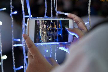 Hand of women with smart phone shooting light in fesival