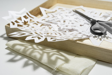 Handmade paper snowflakes and scissors in the box.
