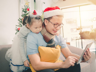 Asian man and little girl wearing a Christmas hat and using a tablet on the sofa, shopping online,playing game on tablet.
