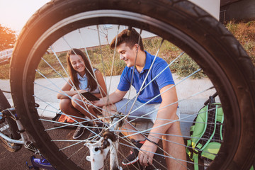 Teenager boy repair tire on bicycle , female friend sitting next to him, using digital tablet for instructions, summer outdoor photo