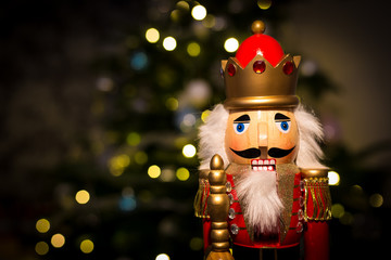 Christmas nutcracker with Christmas tree and lights in background
