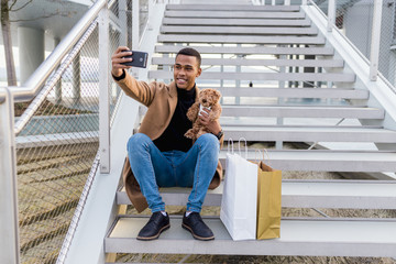 Stylish man taking selfie with toy