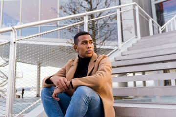 Stylish man sitting on stairs