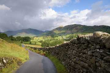 Coutryside road leading into the english landscape of Lake district Cumbria