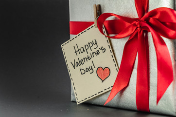 Gift in silver packaging with red ribbon and greetings with Valentine's day.