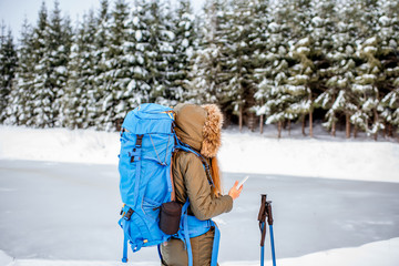 Woman in winter clothes with backpack and tracking sticks enjoying beautiful landscape view on the snowy forest and frozen lake