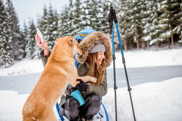 Woman having a break during the winter hiking making selfie with her dog at the snowy mountains near the lake and forest