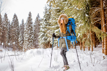 Woman in winter clothes hiking with backpack and tracking sticks in the snowy fir forest