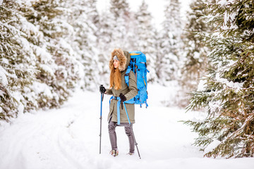 Woman in winter clothes with backpack and tracking sticks walking in the snowy fir forest