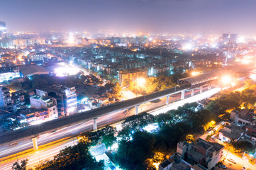 aerial view of the cityscape of Noida gurgoan delhi at night  with the elevated metro track and metro station visible. The city residences and offices are also clearly visible Fototapete