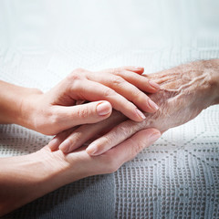 Old and young holding hands on light background, closeup. Care is at home of elderly
