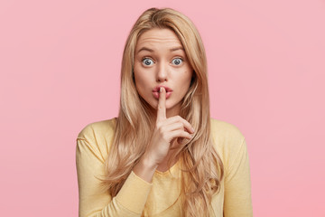 Blonde blue eyed female looks with shock at camera keeps finger on lips, being scared and asks not to make noise, poses in studio. Horizontal shot of beautiful woman makes hush gesture indoor