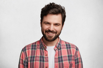 Pleased pleasant looking young student with beard and trendy hairdo wears casual checkered shirt, smiles pleasantly in camera, glad to pass session sucessfully, isolated over white background
